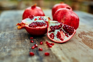 ripe cracked raw pomegranates on a dark wooden background